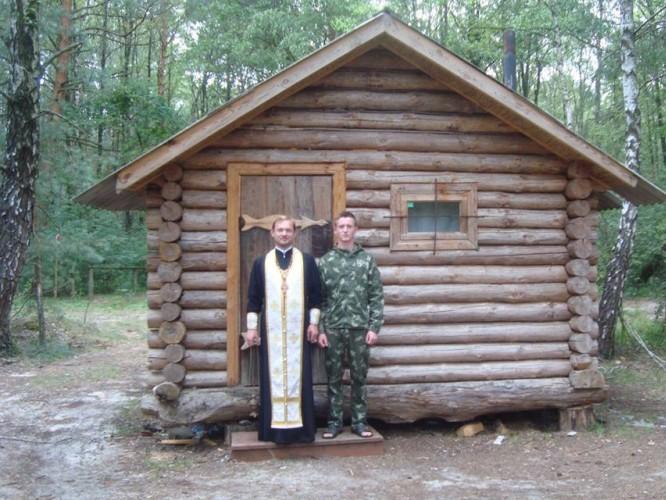 Отець Олександр та рибалка Артем Галух біля освяченої хатини