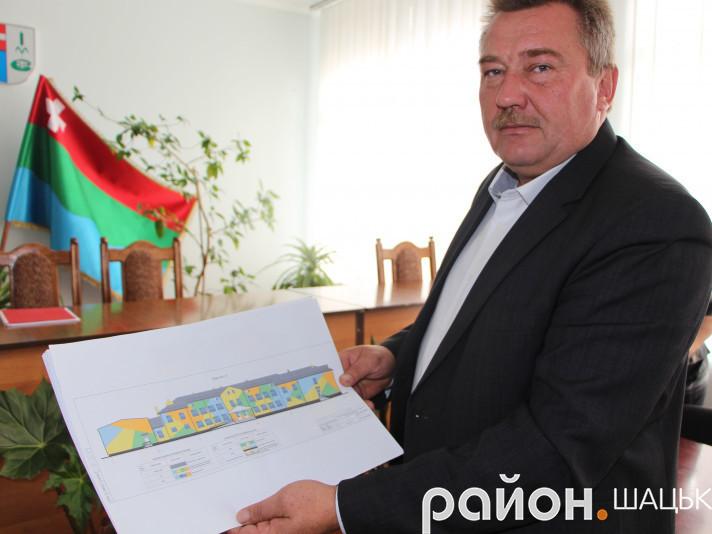 Перший заступник голови Шацької РДА Віктор Плейтух показує проект школи