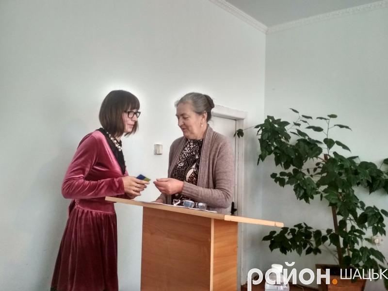 Нова депутатка Ольга Гінайло отримує посвідчення від голови виборчої комісії Ніни Сиротюк